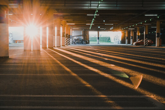 An empty covered  Parking lot with blue license plates lit up by the setting sun