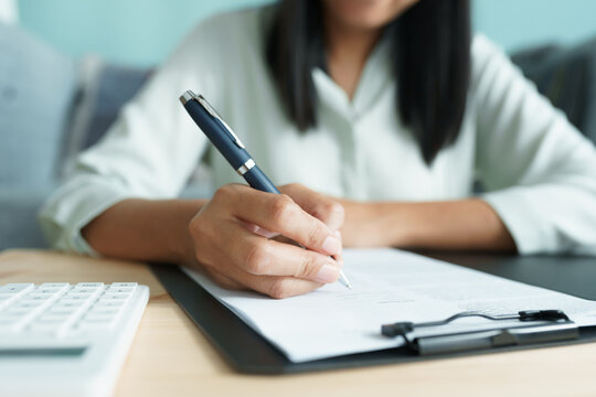 Asian businesswoman is signing agreement with a business contract.