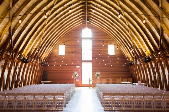 Hall of a wooden barn surrounded by lights prepared for a wedding ceremony