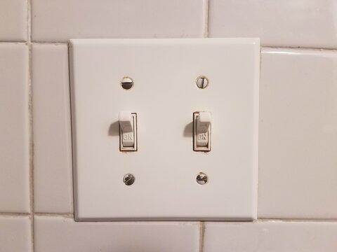 white lightswitch on white bathroom tile