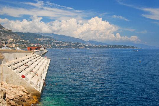 Solarium Beach, Strand am blauen Meer in Monaco, mit Steinstufen zum Sonnen