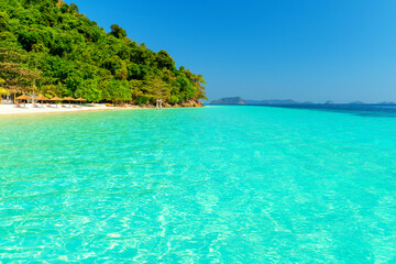 Fototapeten Reef grun Tropical island and white sand beach and clear blue sea and beautiful forest, there are beach beds for sunbathing. And vacationing on holidays. Nyaung Oo Phee Island Myanmar..