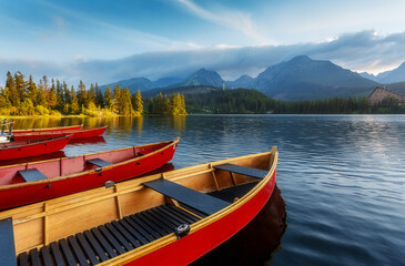 Fotomurales - Beautiful sunny landscape. View on mountain lake with crystal clear azure water in High Tatras. Slovakia. Red Boats on the water glowing in sunlight at sunset. Awesome Autumn landscape. Strbsce pleso