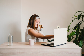 young woman working at home, cuddling Cute small dog. and taking a picture with mobile phone. Stay home concept