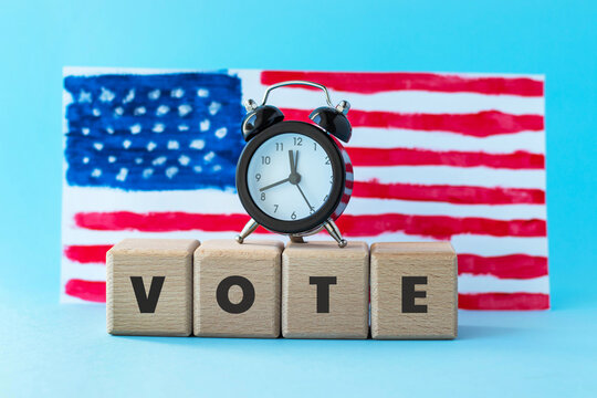 Alarm clock and abstract hand drawn American flag on background. President elections, Memorial Day, 4th of July or Labour Day