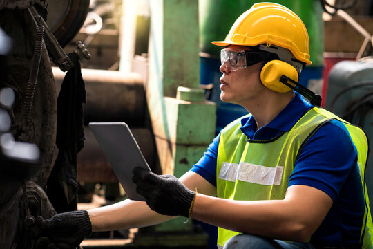 Staff or technicians are checking the operation of the old machine via the tablet.