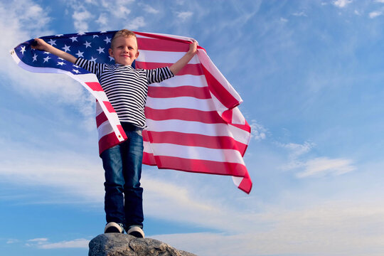 4k. Blonde boy waving national USA flag outdoors over blue sky at summer - american flag, country, patriotism, independence day 4th july