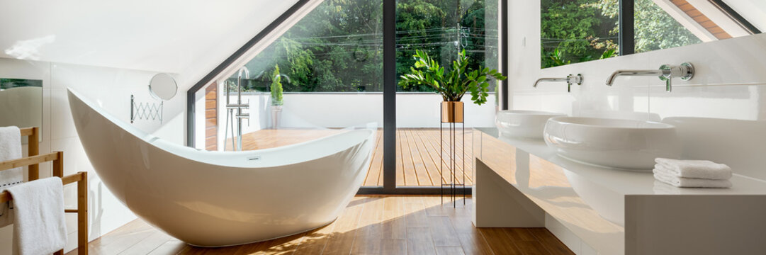 Luxury attic bathroom with bathtub, panorama