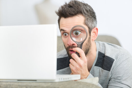 man concentrated looking through a magnifying glass on his laptop
