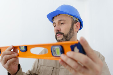 portrait of builder man in uniform standing with spirit level