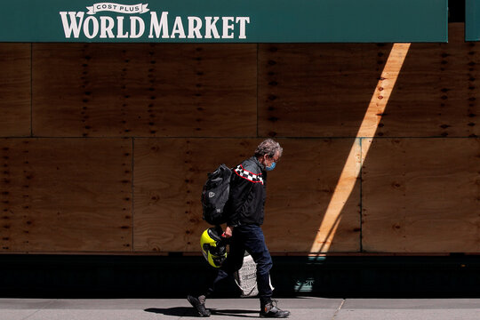 A man walks with a shopping bag outside a Cost Plus World Market, as phase one of reopening after lockdown begins, during the outbreak of the coronavirus disease (COVID-19) in New York