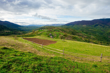 Wall Mural - rural fields on mountain hills. beautiful rural landscape of carpathian nature on a cloudy day. path leads to village in the distance. fence across the grassy meadow