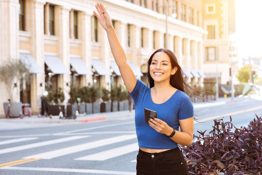 Young woman of color waves her hand to call a ride share in the City - Uber - Lyft - Daytime