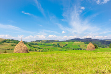 weathered hay stack on the field. idyllic coutryside scenery on a sunny day. wonderful  rural landscape of carpathian mountains