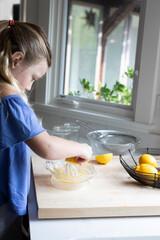 Child making fresh squeezed lemonade in kitchen