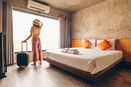 Portrait of tourist woman standing nearly window, looking to beautiful view with her luggage in hotel bedroom after check-in. Conceptual of woman lifestyle when traveling on her vacation.