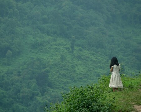 Selective focus shot of a young female standing on top of a cliff looking at the green nature