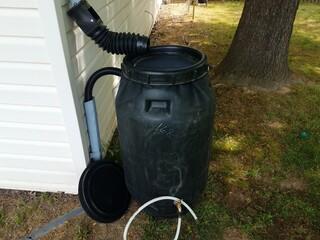 black plastic rain barrel installed on a house