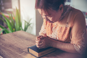 Prayer and bible concept. Asian senior woman praying, hope for peace the world and free from coronavirus, Hand in hand together, believes and faith in christian religion at church.