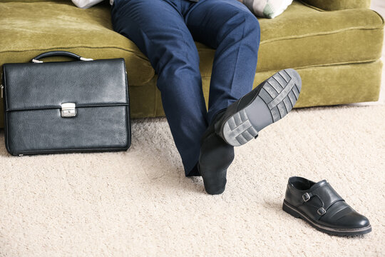 Businessman taking off his shoes at home after long working day