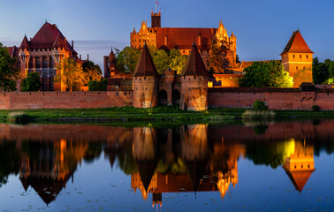 Garden Poster Brown Illuminated walls of the Malbork Castle at night-panorama