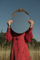 Girl in red dress with mirror in front of her face standing in nature