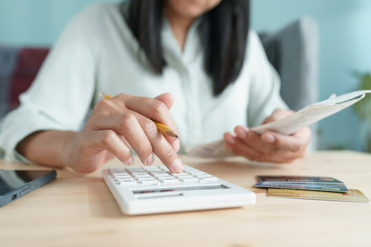 Hand of Asian girl are calculate monthly expenses and credit card at home