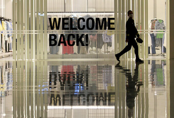 """Worker walks past a """"welcome back!"""" sign during preparations ahead of reopening of a shopping mall, in Jakarta"""