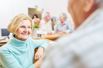Smiling senior woman doing small talk in retirement home