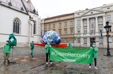 """Green Peace activists carry """"Earth on IV drip"""" installation in front of the Croatian parliament"""