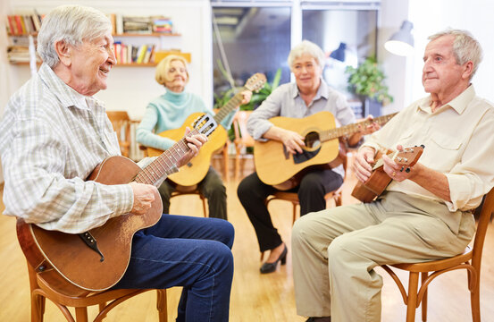 Seniors learn to play the guitar in a guitar course