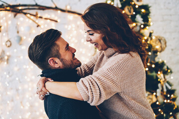 Happy caucasian couple in love having fun together near beautiful Christmas tree