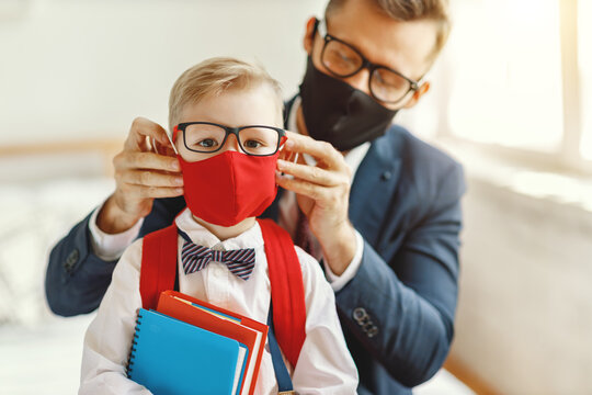 Father putting on protective mask to schoolkid.