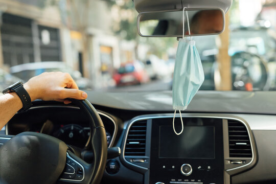 Protective mask hanging from the rear view mirror of a car. View from behind