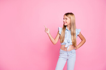 Portrait of positive confident kid girl promoter point index finger copyspace demonstrate advert promotion wear stylish trendy clothes isolated over pastel color background