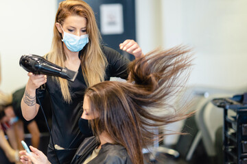 Hairdresser drying her client's hair with a hairdryer wearing protective masks in a beauty centre.