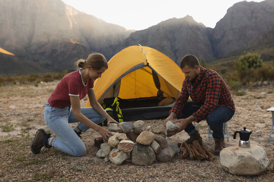 Side view of couple installing rocks for a campfire