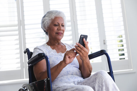 Side view of a senior African american woman sitting in a wheelchair and using her phone