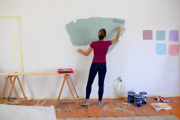 Woman in Social Distancing painting the walls of her house with her dogs