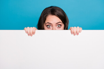 Closeup photo of pretty funny crazy lady hold hands empty advertisement banner peeking eyes hiding face tricky read novelty surprise placard isolated blue color background
