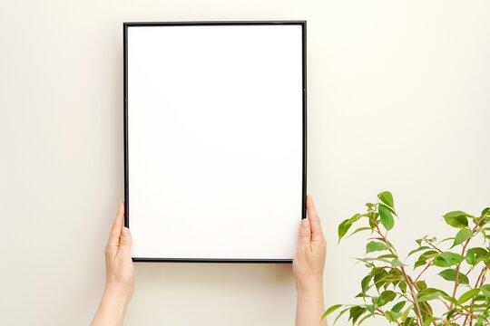 Styled stock photo, blank black frame mockup and greenery, hands holding frame, minimalist interior, green plant, artwork display.