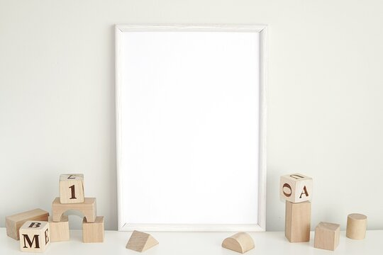 White frame mockup for nursery or kids room, blank photo frame and wooden cubes.