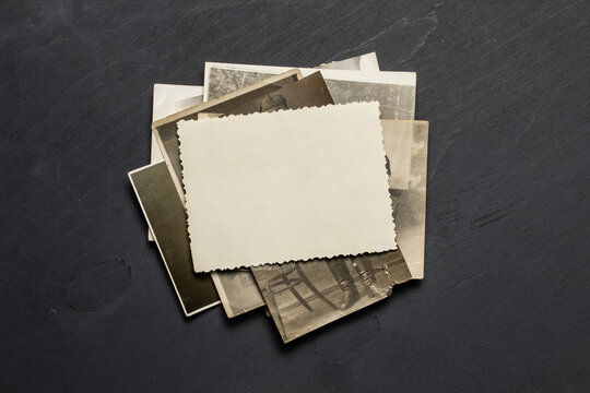 Vintage blank paper sheet over pile of old retro family photo cards