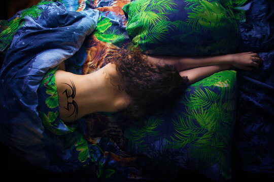 girl with tattoo on the lower back lies on the bed, the view from the top
