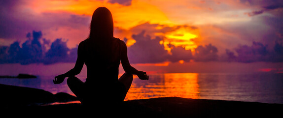 Woman meditating, relaxing in yoga pose at sunset, zen meditation. Silhouette in lotus pose. Mind body spirit concept