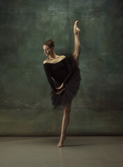 Balanced. Graceful classic ballerina dancing, posing isolated on dark studio background. Elegance...