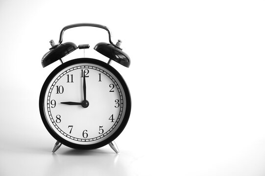 Black vintage alarm clock on table. White background. Wake up concept. An image of a retro clock showing 09:00 pm/am.