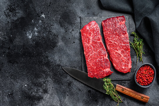 Marble beef Denver steak with herbs. Organic meat. Black background. Top view. Copy space