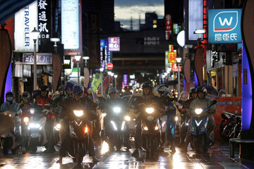 People riding motorbikes wait on the red light during rush hour in Keelung