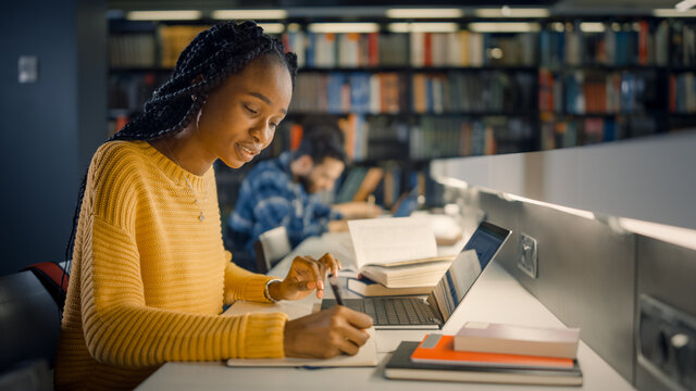 University Library: Gifted Beautiful Black Girl Sitting at the Desk, Uses Laptop, Writes Notes for the Paper, Essay, Study for Class Assignment. Diverse Group of Students Learning, Studying for Exams.